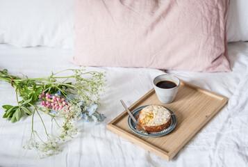 Frühstück im Bett mit süßem Kuchen und Kaffee mit Blumen