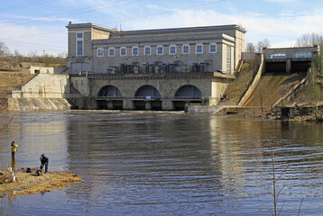 people are fishing on river Narva against the background of hydroelectric power station