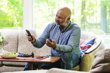 Mature diabetic man testing his blood sugar and using a smartphone