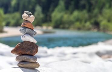 Gestapelte Steine vor traumhafter Kulisse am Fluss