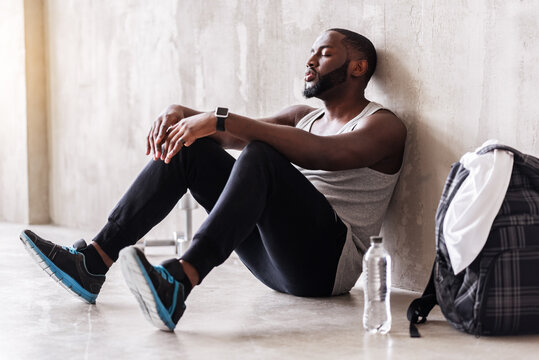 Calm bearded sportsman having rest time after training