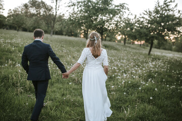 bride and groom walking on a field from behind