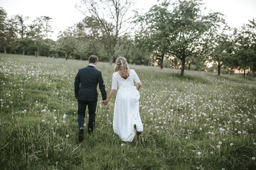 bride and groom walking on field from behind
