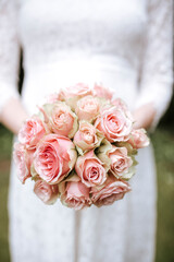 bride holding bouquet with roses