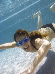 femme souriante en maillot de bain sous l'eau