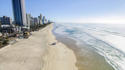 Aerial view of lifeguards people walking on the beach at Surfers Paradise at sunrise.