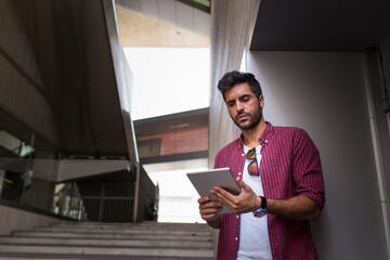 Handsome man with tablet on street