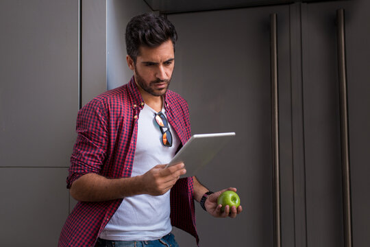Trendy young man standing with apple and watching tablet while leaning on wall of building.