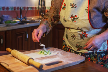An elderly woman in an apron prepares pies in the kitchen