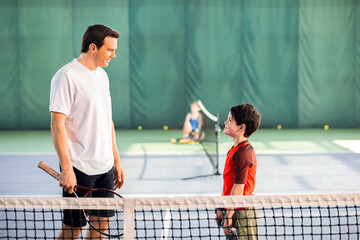 Joyful man playing tennis with his son