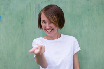 A girl with freckles in a white T-shirt invites, stretching her arm forward. Come after me.