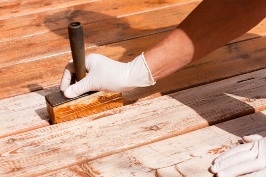 Deck maintenance apply stain on wooden decking