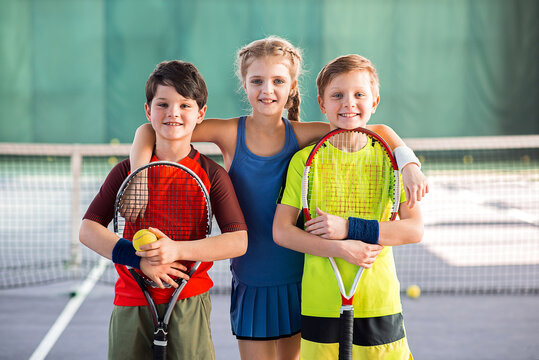 Cheerful kids having fun on tennis court