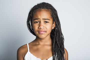 Adorable sad african little girl on studio gray background