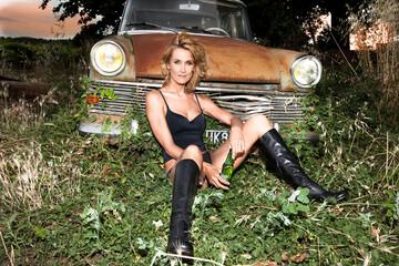 femme assise en sous-vêtements devant une voiture ancienne