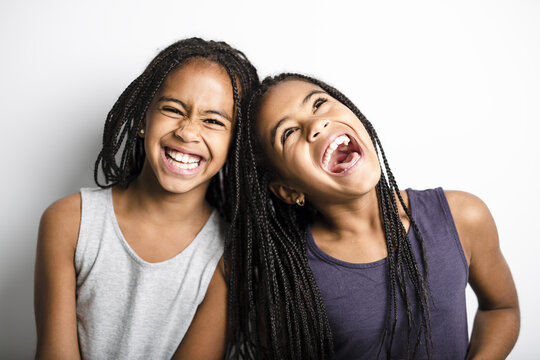 Adorable african twin little girls on studio gray background