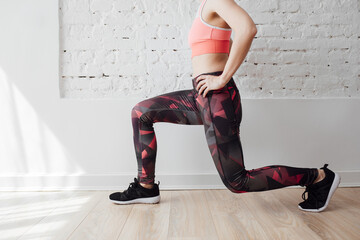 Cropped unrecognisable sportswoman in tights doing lunges exercise.