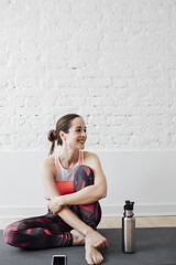 Pretty Caucasian woman athlete sitting on mat and smiling.