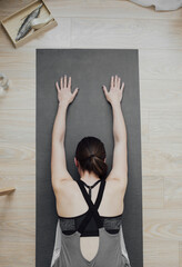 From above photo of woman doing yoga on mat.