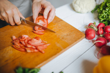 Woman hands cutting fresh red tomato on wooden board closeup. White table background.