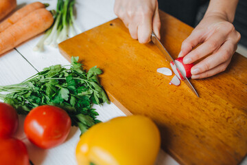 Woman hands cutting fresh red organic radish on wooden board closeup. White table background.
