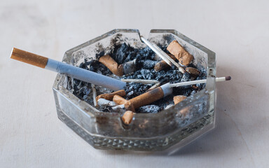 A cigarette with a filter in a dirty ashtray with cigarette butts, conceptual photography,