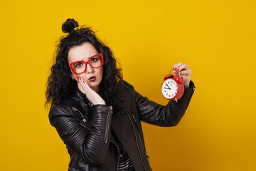 Beautiful surprised young woman with alarm clock standing in front of yellow background.