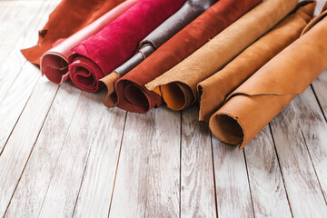 Multicolored leather in rolls on wooden background.