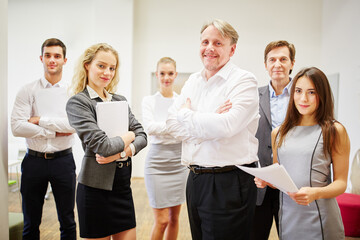 CEO and business team standing with crossed arms