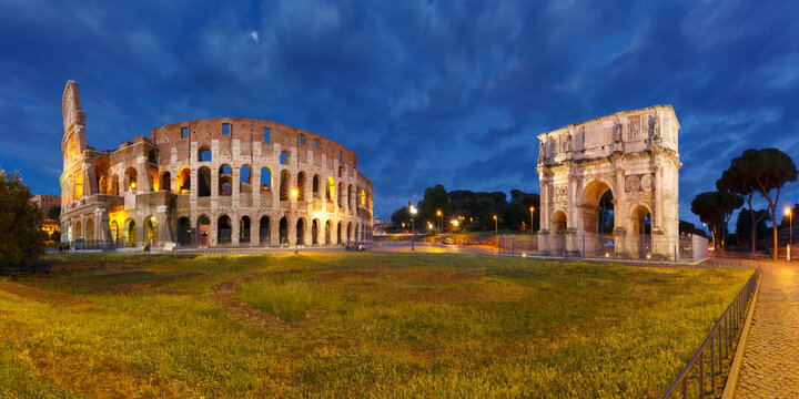 Panorama of The Arch of Titus and Colosseum or Coliseum at night, also known as the Flavian Amphitheatre, the largest amphitheatre ever built, in the centre of the old city of Rome, Italy.