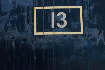 black corroded metal with number 13 from old train