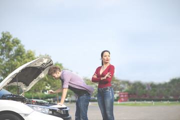 A couple has engine failure car breakdown, Woman feeling angry frustrated suffering. Man try to fix engine.