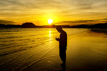 silhouette of young man praying on the beach with  golden sunset
