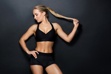 young woman in black sportswear posing in gym