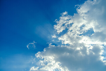 Crepuscular light with white clouds on blue sky