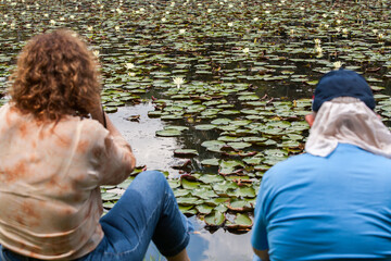 Two people looking to a water lily lake