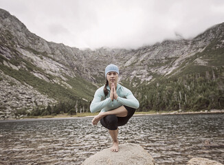 A woman practices yoga on the shore of Chimney Pond in Maine's Baxter State Park.