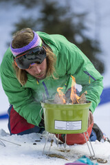Skier preparing a primitive barbecue using a shovel as grill in the outdoors