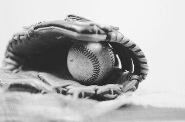 Black and white vintage baseball image of old leather mitt and antique ball in glove.  Great sports background or graphic