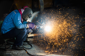 Gouging Welding,  Industrial welder wear safety protective mask gouging weld Gear construction repair and fix imperfection weld for new part in factory.