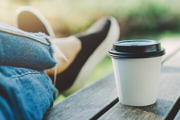 Young woman walking at park and drinking coffee to go, Hipster woman enjoying coffee while resting at park