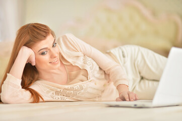 young woman lying on floor with laptop