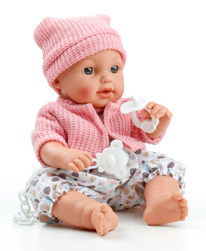 Toy doll child, in pink blouse with pacifier on isolated background