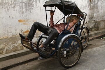 Poor man resting on the streets of Cambodia during the heat, streets of Asia