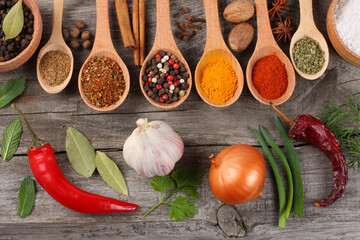 herbs and spices, onion, garlic and chili pepper on old wooden background. Top view