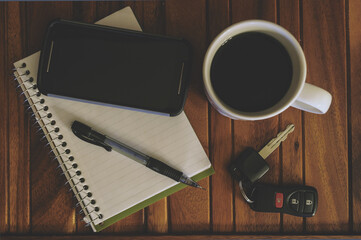 Cup Of Coffee, Cell Phone, Notepad, Pen, And Keys On A Wood Table