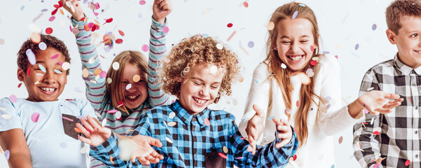 Smiling kids playing with confetti