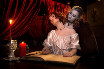 Vampire girl bites the victim's neck in red studio