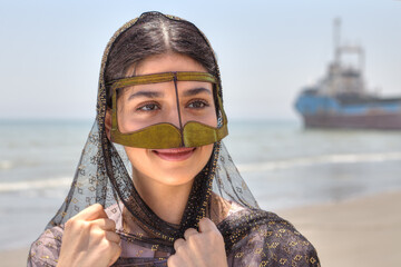 Iranian girl in traditional Muslim mask of southern Iran, smiling.