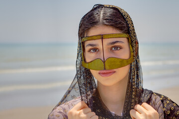 Girl in mask bandari woman, beach of Persian Gulf, Iran.